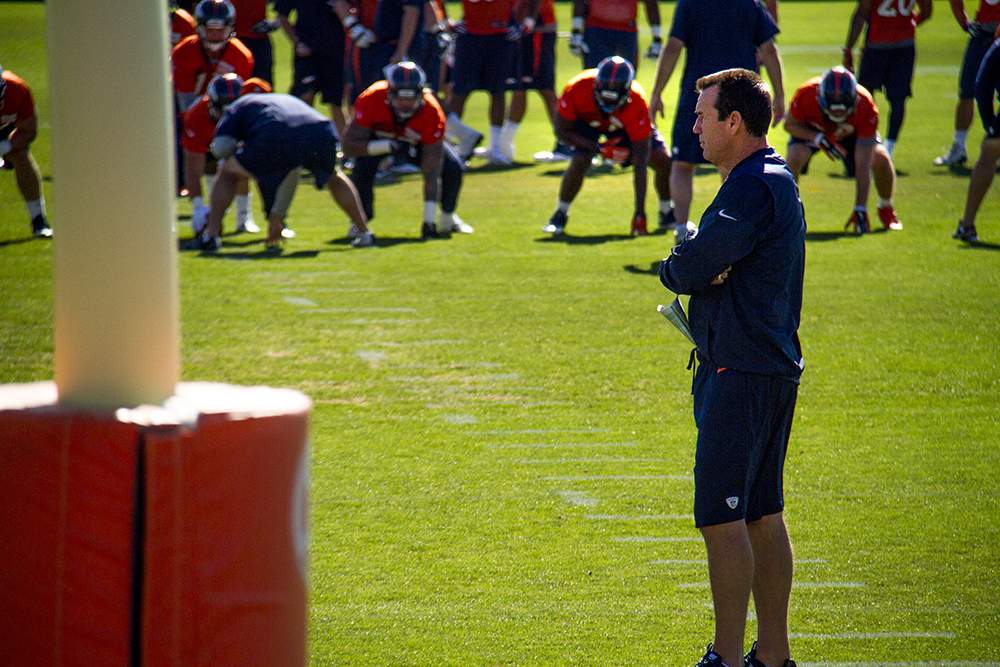 Gary Kubiak watches as his team runs drills at Denver Broncos Training Camp. (Kevin J. Beaty/Denverite)  broncos; football; training camp; sports; kevinjbeaty; denver; denverite; colorado;