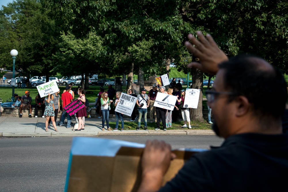 A group from Harm Reduction Action Center gathered on Colfax and Broadway to demonstrate for International Overdose Awareness Day. (Chloe Aiello/Denverite)