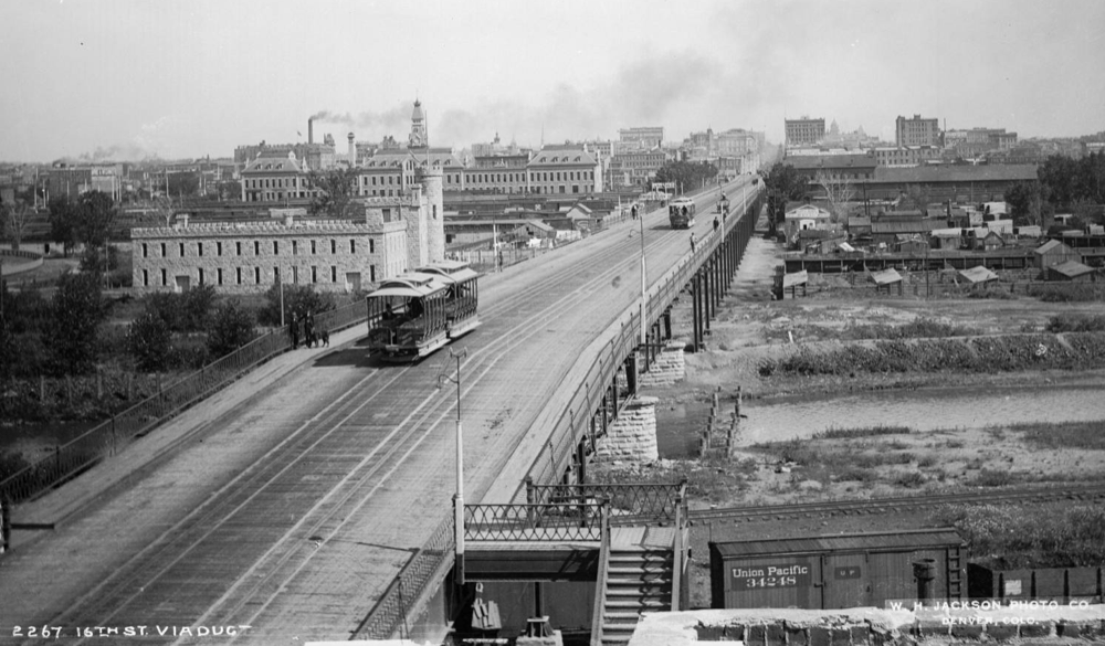 "16th Street used to cross the South Platte River on this viaduct, shown circa 1890s. The castle-looking building to the left is the present site of ""Stoner Hill"" in Commons Park. Union Station is behind it. (Denver Public Library/William Henry Jackson Collection/CHS.J41)"