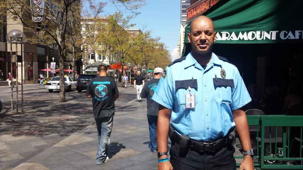 """Warner Smith poses in the uniform of the new Downtown Denver Partnership's """"private security team."""" (Adrian D. Garcia/Denverite)"""