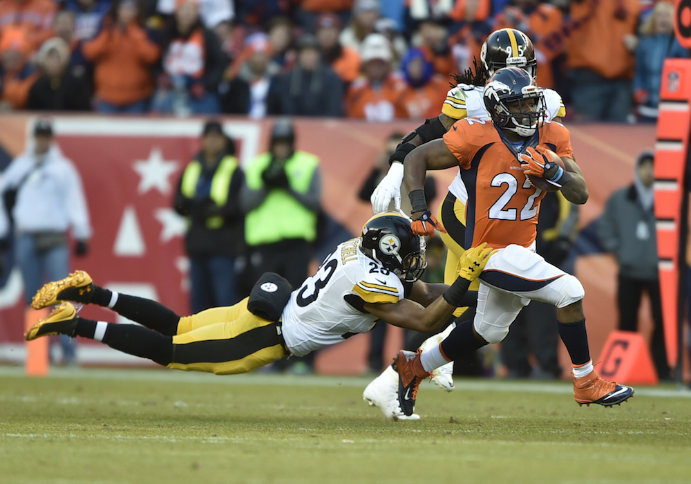 Denver Broncos running back C.J. Anderson (22) carries for 7 yards as Pittsburgh Steelers safety Mike Mitchell (23) attempts to bring down Anderson during second quarter action  in the  NFL AFC Divisional playoff game at Denver, Colo. January 17, 2016. (© Eric Lars Bakke/ Denver Broncos)