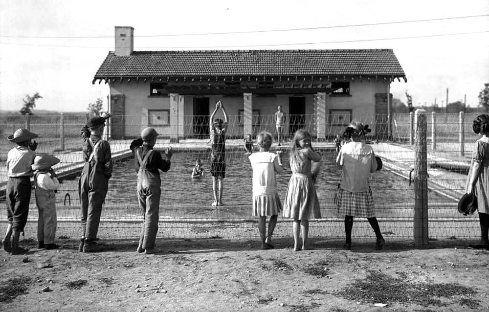 Children stand behind a wire fence and watch a boy in a bathing suit prepare to dive into the Children's Pool at Elyria Playgrounds (Elyria Park) at 48th and High Streets in the Elyria Swansea neighborhood of Denver, Colorado. Shows a stucco building with tile roof and brick quoins. An adult in a swimsuit watches the diver; other swimmers stand in the water and sit at the pool's edge. Between 1918. (Denver Public Library/Western History Collection/X-28900)  summer; pool; historic; denver public library; dpl; archive; archival; denverite