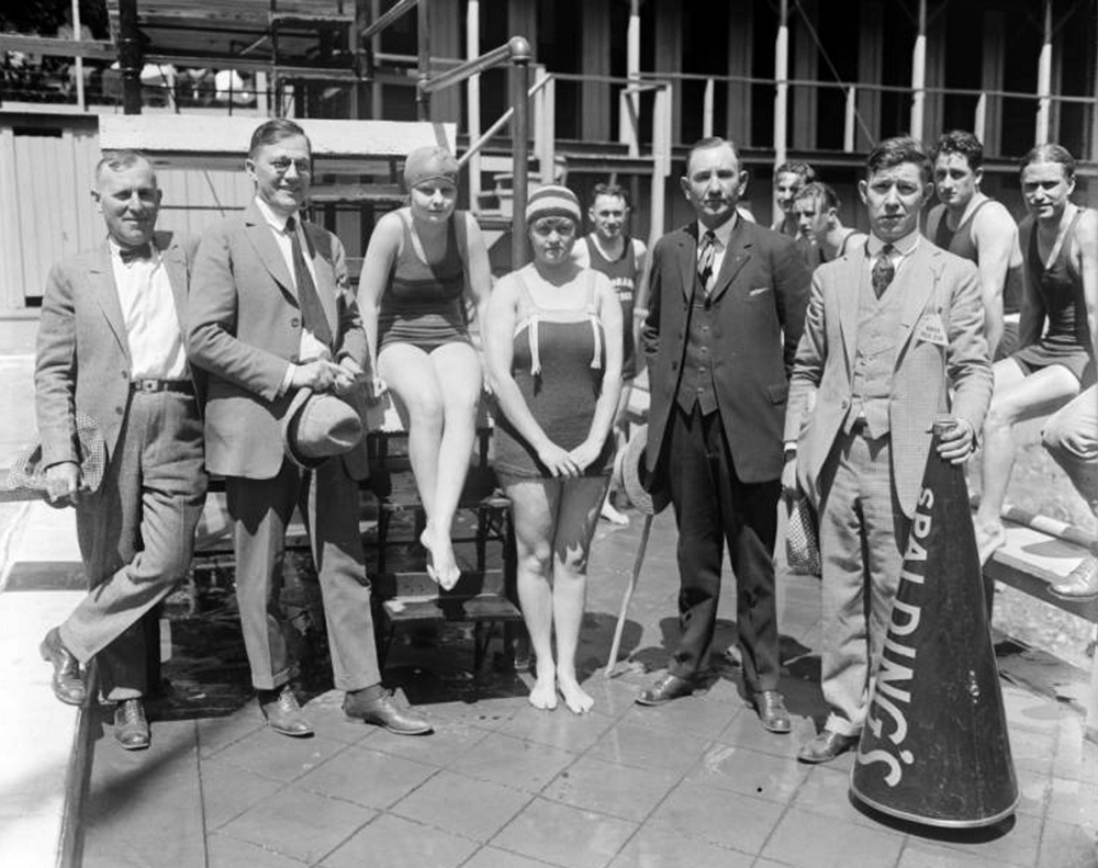 "Four men pose with two female swimmers in front of a pool in Denver, Colorado. The women wear bathing suits and caps. One man wears a badge that reads: ""Denver Press Club"", and holds a megaphone with ""Spalding's"" painted on it. Between 1920 and 1940. (Harry Mellon Rhoads/Denver Public Library/Western History Collection/Rh-1414)  summer; pool; historic; denver public library; dpl; archive; archival; denverite"
