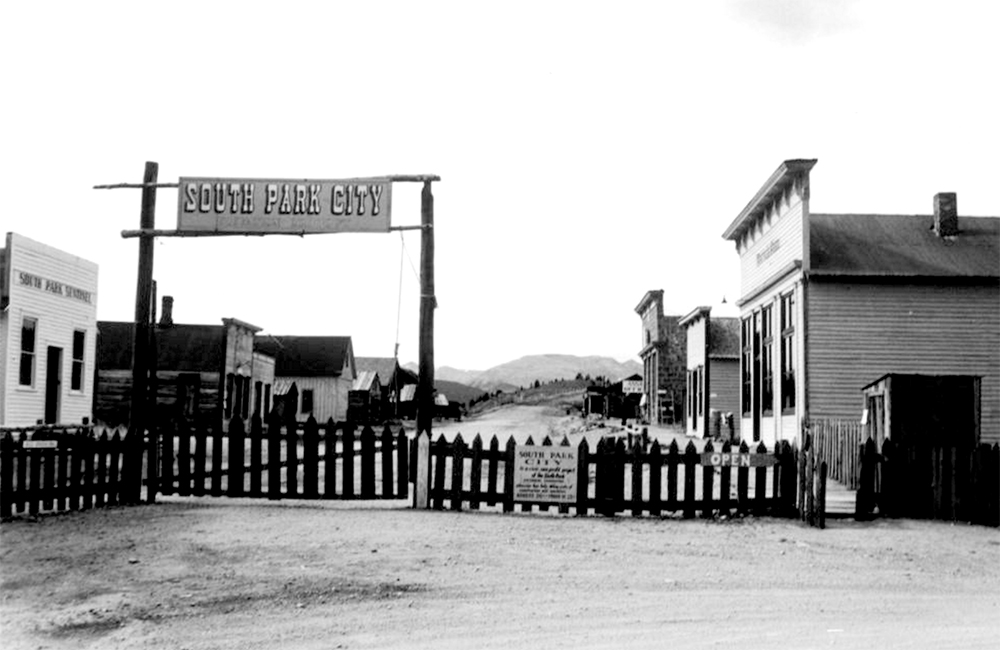 "South Park City in the town of Fairplay, Colorado, Park County, is enclosed by a wood-picket fence with a sign over the gate. Commercial storefronts are on both sides of the unpaved street. Signs: ""South Park Sentinel"" ""Open."" Between 1960 and 1970. (Denver Public Library/Western History Collection/X-8356)  south park; fairplay; history; historic; denver public library; dpl; archive; archival; denverite;"