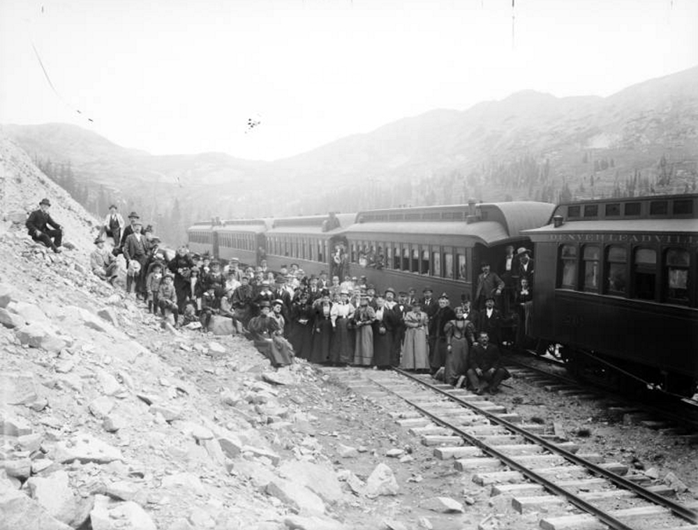 A group of passengers pose on the railroad tracks next to a Denver, Leadville and Gunnison train on the Denver & South Park near alpine tunnel. Between 1890 and 1898. (Harry H. Buckwalter/History Colorado/90.156.403)  south park; fairplay; history; historic; denver public library; dpl; archive; archival; denverite;