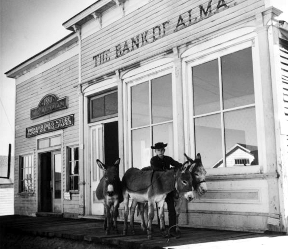 "A boy stands with three burros on a wood-plank sidewalk in front of two commercial storefront buildings along a South Park City Street in Fairplay, Colorado, in Park County. Signs: ""The Bank of Alma"" ""1880 W. E. Merriam"" ""Pioneer Drug Store Paints Oil Wallpaper."" October 5, 1958. (Helen May Hoyt/Denver Public Library/Western History Collection/X-8360)  south park; fairplay; history; historic; denver public library; dpl; archive; archival; denverite;"