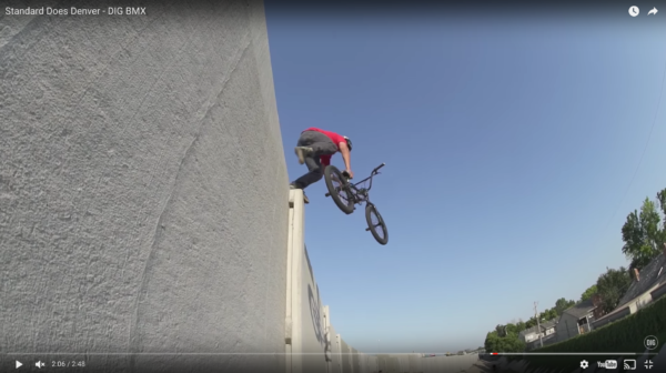 A BMX rider launches off a highway wall near Denver in this YouTube screenshot. (YouTube/Standard Byke)