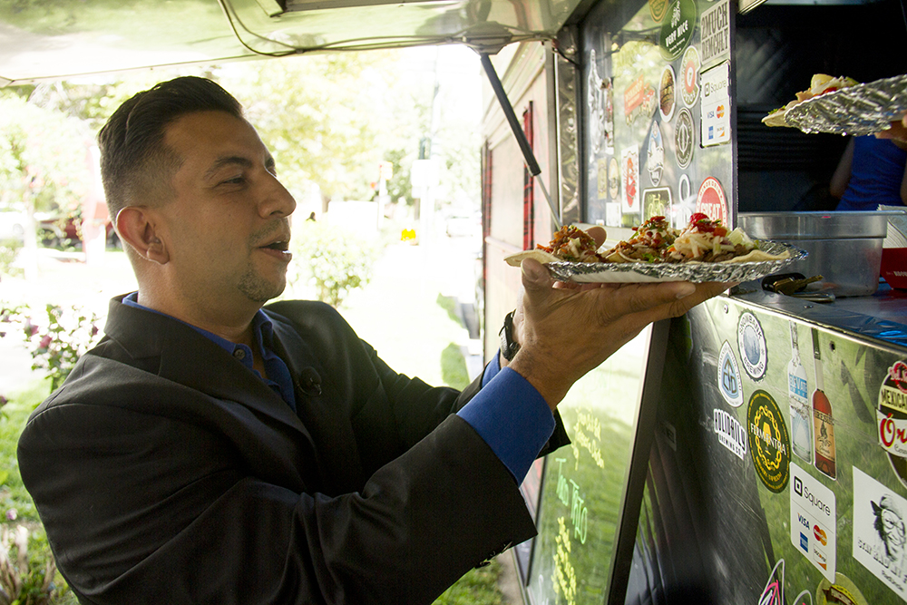 Denver City Councilman Paul Lopez gets food from taco truck parked in protest in front of the Denver Trump campaign headquarters on Sept. 2, 2016. (Kevin J. Beaty/Denverite)  food; tacos; politics; donald trump; hillary clinton; hispanic; protest; election; vote; kevinjbeaty; denverite; denver; colorado;