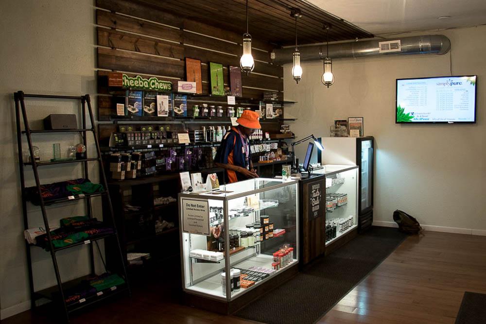 Maat Khan behind the counter at Simply Pure. (Chloe Aiello/Denverite)