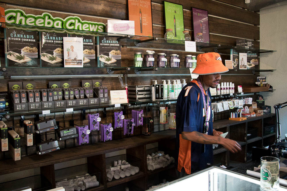 Simply Pure dispensary with Maat Khan, budologist and executive assistant, behind the counter. (Chloe Aiello/Denverite)