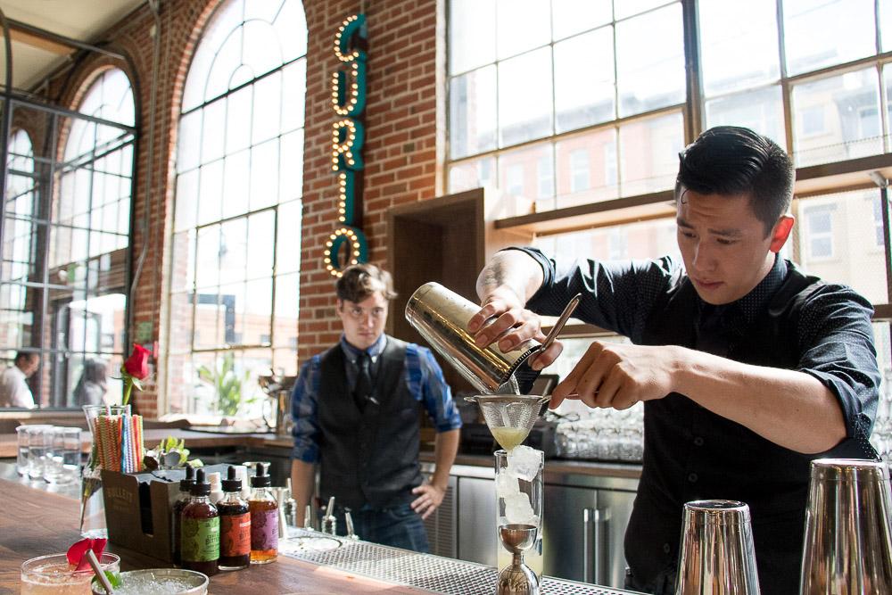 TJ Vong, bar lead at Curio, pours a drink at Central Market. (Chloe Aiello/Denverite)