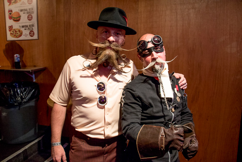 Al Underwood and fellow competitor and friend, James McMahon at A little girl gets in the spirit at Mr. Jock Strap at the Great American Beard and Moustache Championship. (Chloe Aiello/Denverite)