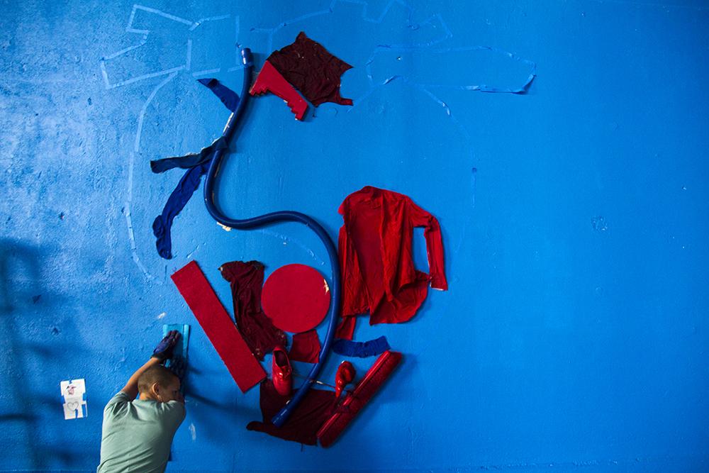 Artist Paige Madden leans against a found object as the glue behind it hardens on the wall. (Kevin J. Beaty/Denverite)  mural; graffiti; art; i-70; i70; elyria; swansea; denver; colorado; cdot; kevinjbeaty; denverite;