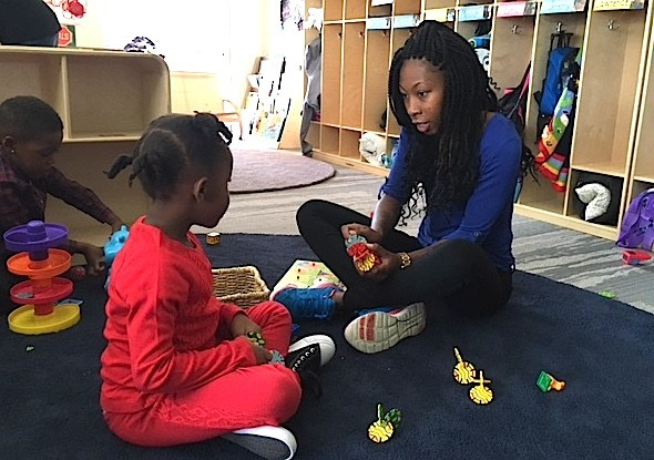 Assistant teacher E'Monna Moore plays with a child at the Sewall Child Development Center at the Dahlia Campus. (Ann Schimke/Chalkbeat)