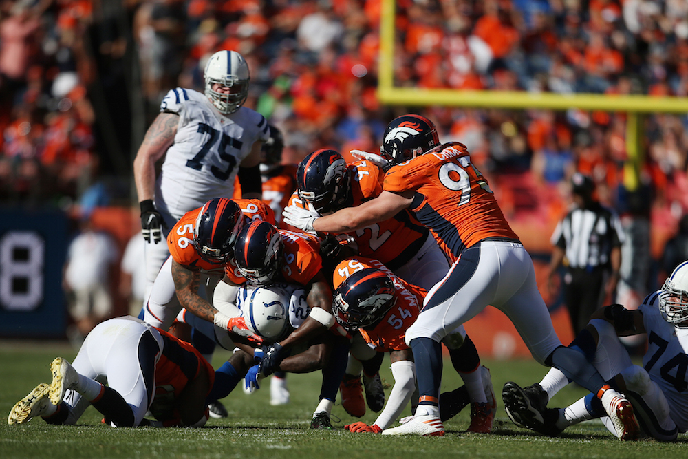 Denver Broncos defense gang tackles Indianapolis Colts running back Frank Gore (23) during third quarter action against the Indianapolis Colts during the game at Sports Authority Field at Mile High in Denver, CO, September 18, 2016. Photo by Gabriel Christus