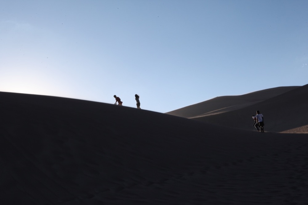 Travelers climb a dune at Great Sand Dunes National Park. (Andrew Kenney/Denverite)