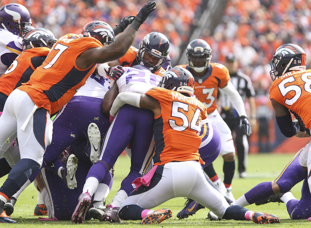Denver Broncos linebackers Todd Davis (51) and Brandon Marshall (54) team up to stop Minnesota Vikings running back Adrian Peterson (28) during first quarter action in the NFL game at Sports Authority Field in Denver, CO, October 4, 2015. (Photo credit: Ben Hays/Denver Broncos)