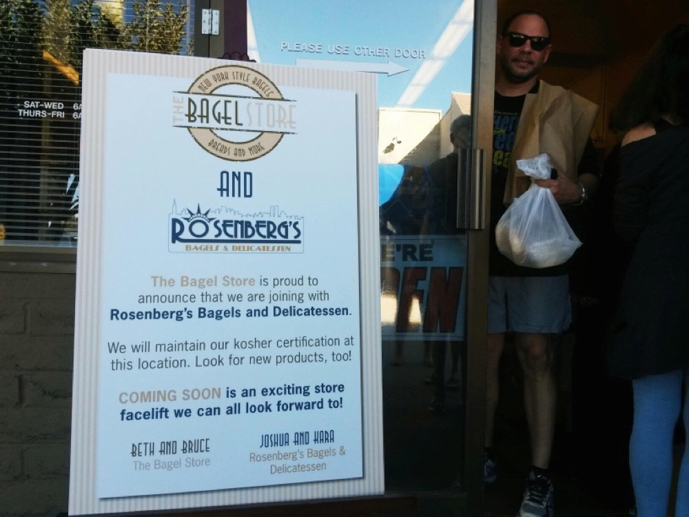 A sign at The Bagel Store announces that the business is merging with Rosenberg's. (Ashley Dean/Denverite)