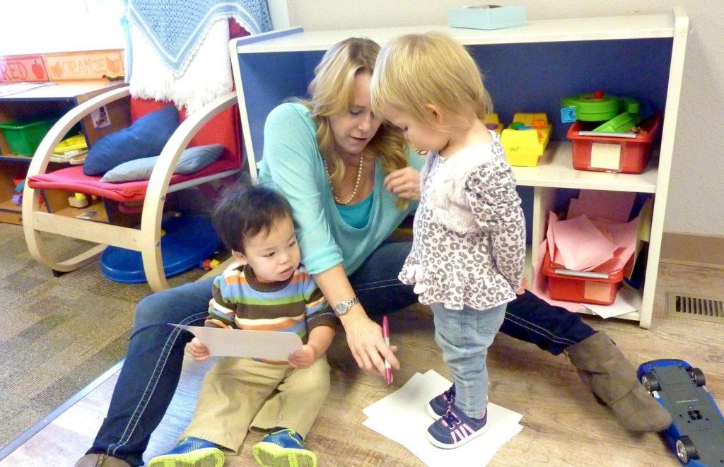 Jodi Bell, lead toddler teacher at Teaching Tree Early Childhood Learning Center in Loveland, outlines a child's foot. (Ann Schimke/Chalkbeat)