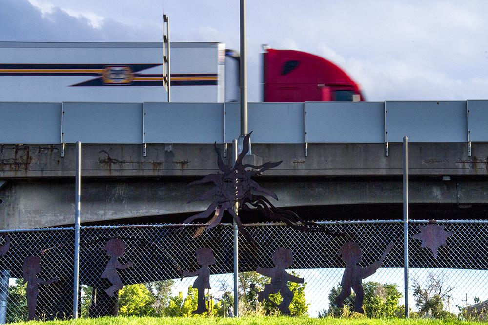A truck speeds over Swansea Elementary. (Kevin J. Beaty/Denverite)  elyria; swansea; gloveville; development; i70; i-70; highway; infrastructure; kevinjbeaty; denver; denverite; colorado; cdot;