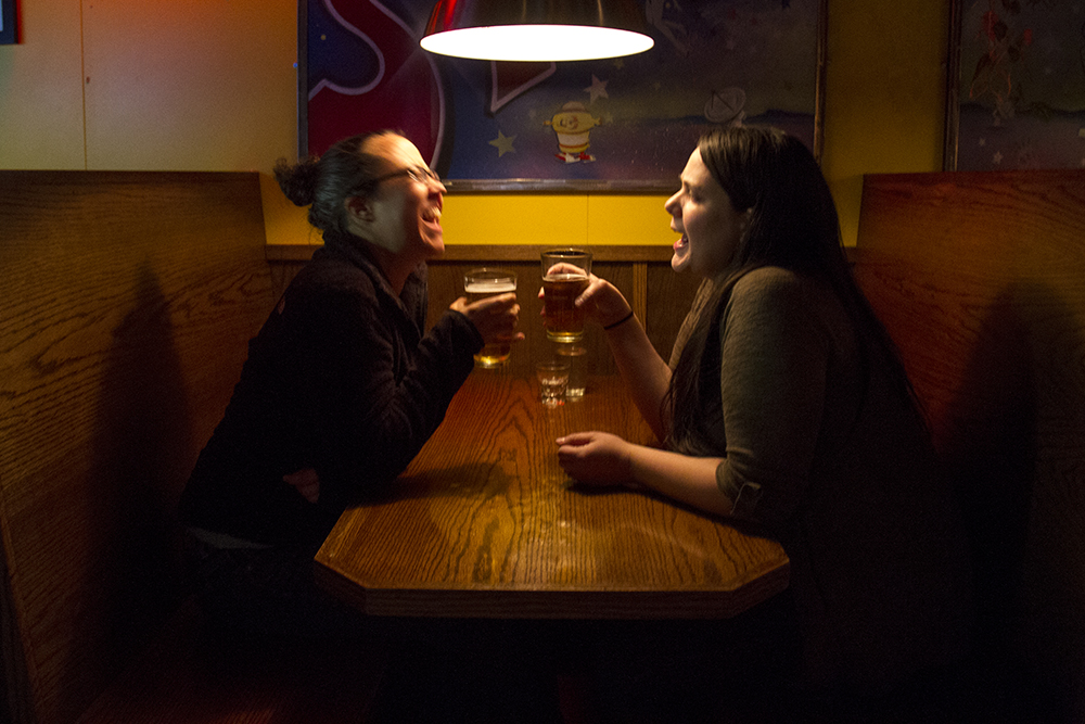 Lilly O'Shea (left) and Allison Ives drink a beer at Satellite on Colfax. (Kevin J. Beaty/Denverite)  beer; nightlife; kevinjbeaty; bars; denverite; denver; colorado;