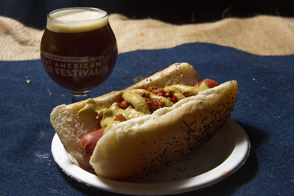 A smoked chili dog from Russell's Smokehouse topped with house-made mustard and paired with Smoke Peat Every Day, the Scotch ale from Haymarket Pub and Brewery. (Kevin J. Beaty/Denverite)  food; gabf; great american beer fest; beer; kevinjbeaty; denverite; denver; colorado;