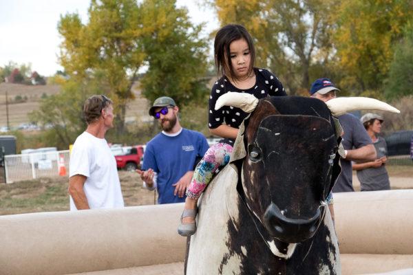 Ayana rides a bull. (Chloe Aiello/Denverite)