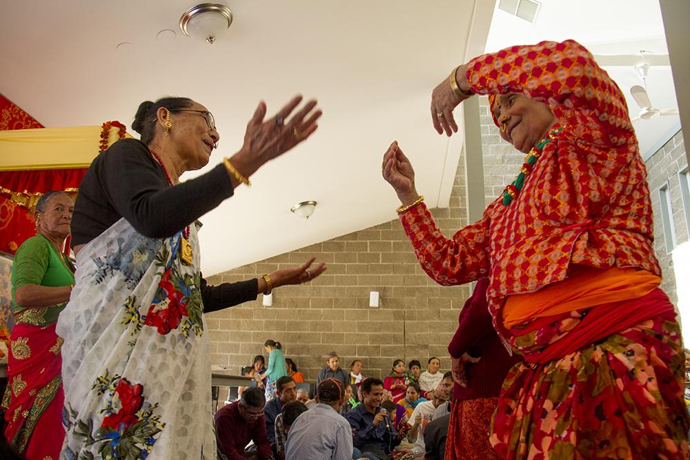 Ganga Adhikari dances to the music. The Hindu Durga Puja celebration held in Aurora's Lowry Park pavilion by the local community of Bhutanese/Nepali refugees. (Kevin J. Beaty/Denverite)  bhutanese refugees; nepali; hinduism; religion; puja; kevinjbeaty; denver; denverite; colorado;