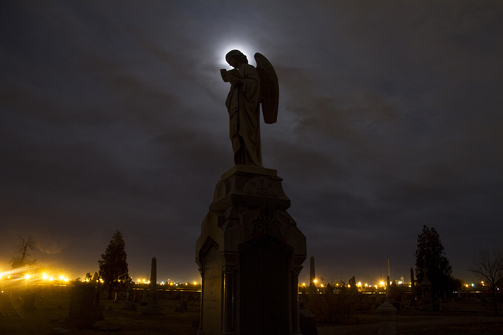 Denver founding father Richard Whitsitt's grave, an angel silhouetted by the moon at Riverside Cemetery. (Kevin J. Beaty/Denverite)  riverside cemetery; history; kevinjbeaty; denverite; denver; colorado;