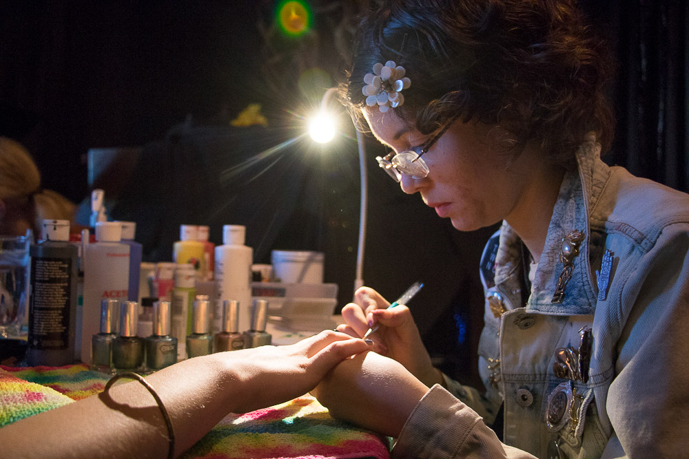 Yasmine Hill of Don't Be So Cuticle gives Nuffer Rodriguez a manicure at Witch Collective market. (Chloe Aiello/Denverite)