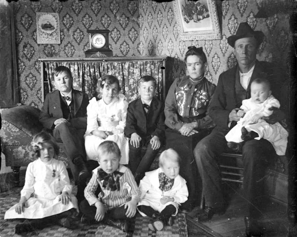 Group portrait of a man, woman, boys, girls, and baby, in Denver, Colorado; interior decor includes a mantle clock, costume includes applique. Between 1904 and 1915. (Charles Lillybridge/History Colorado/90.152.1125 DPLY)  history colorado; historic; denver public library; dpl; archive; archival; denverite