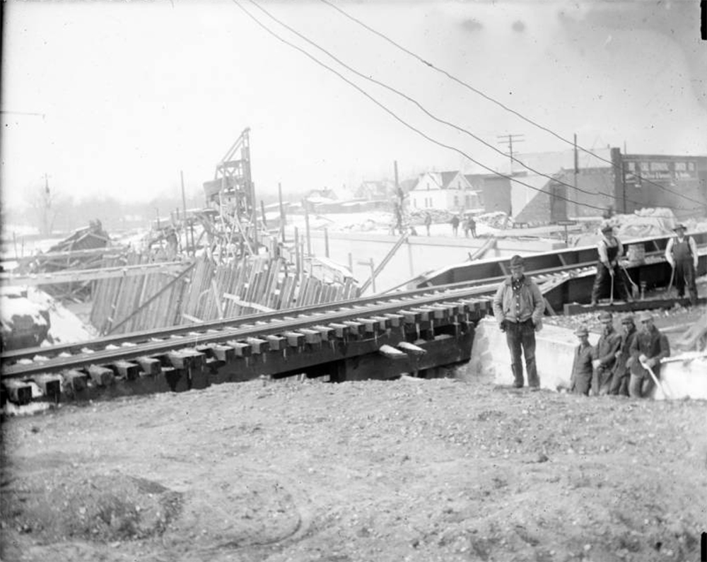 View of Alameda Avenue underpass construction in Denver, Colorado; shows men, railroad tracks, concrete forms, and houses. Circa 1910. (Charles Lillybridge/History Colorado/90.152.778 DPLY)  history colorado; historic; denver public library; dpl; archive; archival; denverite