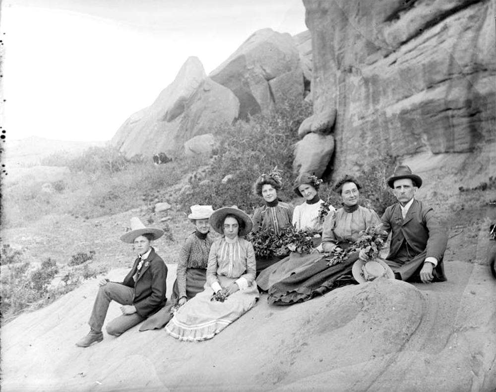 Outdoor portrait of a group of men and women at possibly Creation Park (Red Rocks) near Morrison (Jefferson County), Colorado. A few of the women hold bunches of greenery and wear decorated hats. Between 1904 and 1915. (Charles Lillybridge/History Colorado/90.152.1616 DPLY)  history colorado; historic; denver public library; dpl; archive; archival; denverite