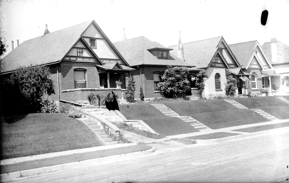 "View of brick houses, with shingle imbrication, covered porches, and arched windows, in Denver, Colorado. Address by a United States flag reads: ""2025."" Between 1904 and 1915. (Charles Lillybridge/History Colorado/90.152.783 DPLY)  history colorado; historic; denver public library; dpl; archive; archival; denverite"
