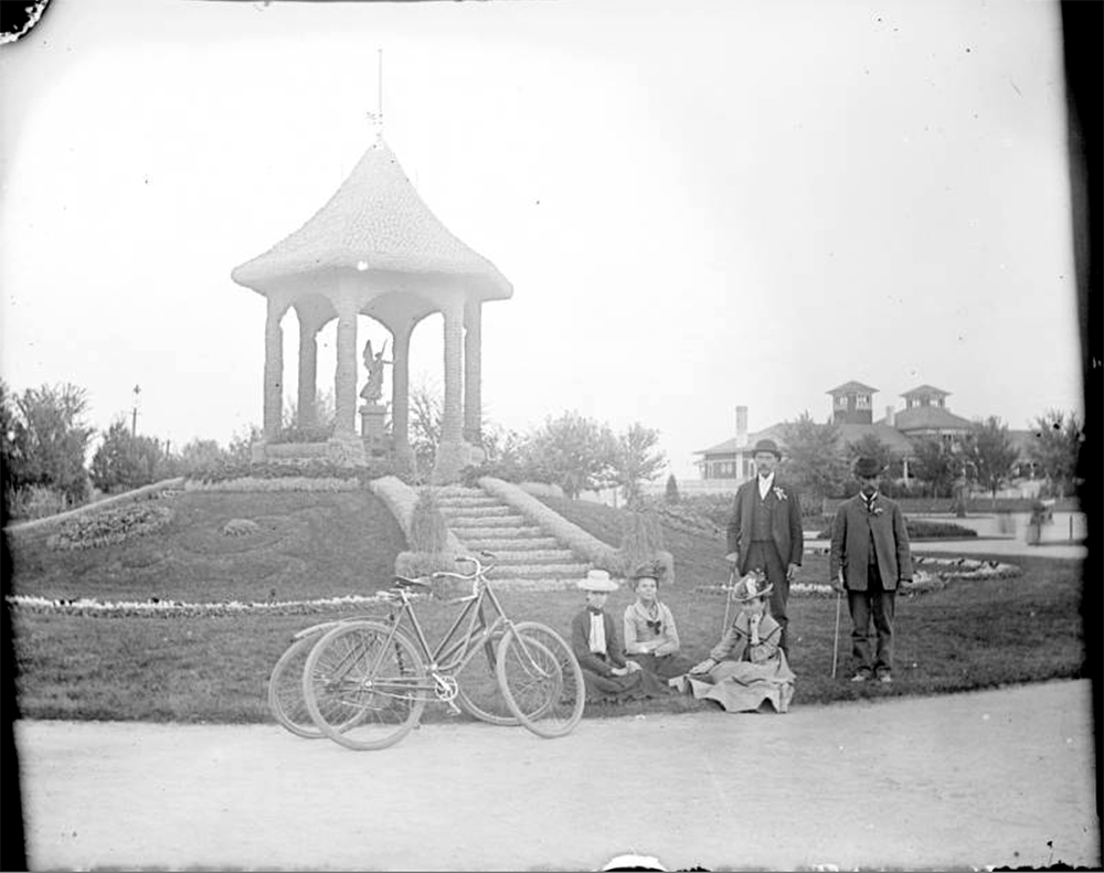 Men and women pose near two bicycles in City Park, Denver, Colorado. A gazebo with an angel statue is nearby. The pavilion is in the distance. Between 1904 and 1915. (Charles Lillybridge/History Colorado/90.152.1626 DPLY)  history colorado; historic; denver public library; dpl; archive; archival; denverite