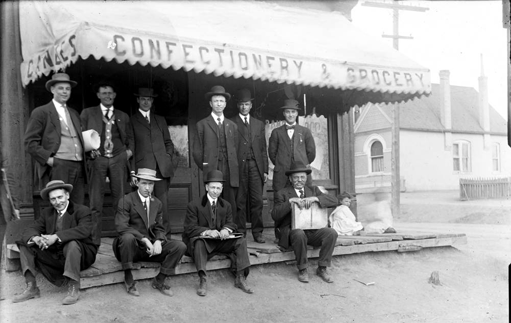 "A group of men stand and sit on the sidewalk near a grocery store in Denver, Colorado. One man holds a briefcase. A sign on the awning reads: ""Confectionery & Grocery"". Between 1904 and 1915. (Charles Lillybridge/History Colorado/90.152.1641 DPLY)  history colorado; historic; denver public library; dpl; archive; archival; denverite"