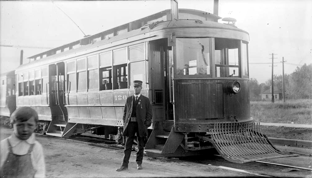 View of streetcar number 126, in Denver, Colorado, at (possibly) the turnaround wye at the end of the Valverde Line at South Lipan Street and West Alameda Avenue; shows a man in a conductor uniform, a boy is to the side. Between 1904 and 1915. (Charles Lillybridge/History Colorado/90.152.1 DPLY)  history colorado; historic; denver public library; dpl; archive; archival; denverite
