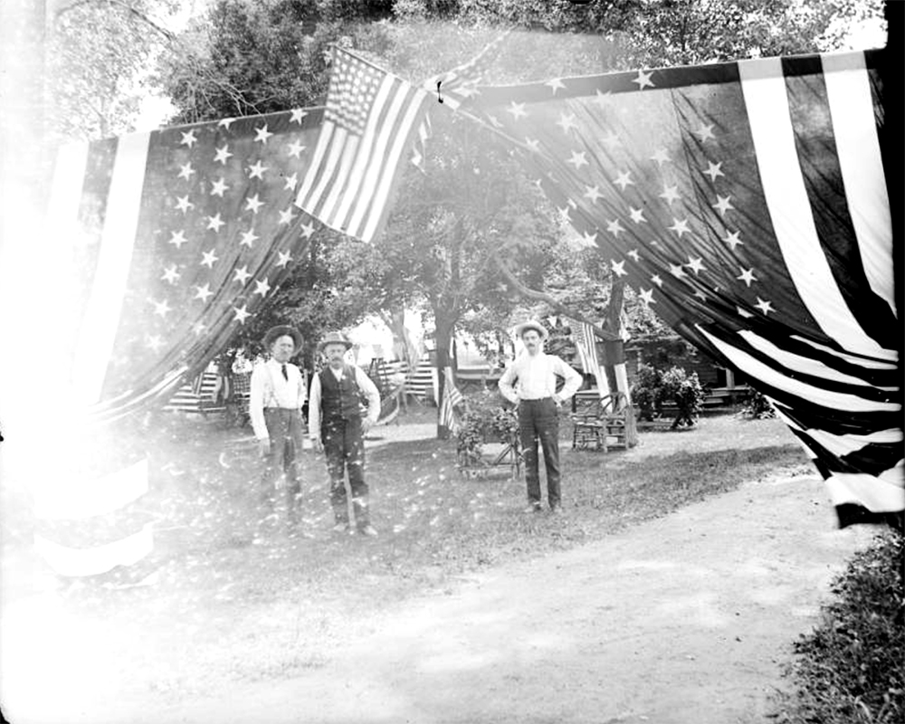 Men pose in City Park, in Denver, Colorado, by United States flags and bentwood chairs during a Fourth of July festival. Between 1904 and 1915. (Charles Lillybridge/History Colorado/90.152.52 DPLY)  history colorado; historic; denver public library; dpl; archive; archival; denverite