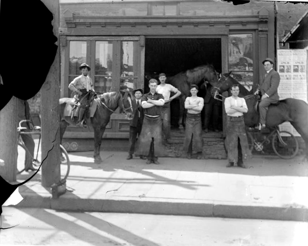 A group of men pose near possibly a blacksmith's shop in Denver, Colorado. Two men are on horseback and other men wear long aprons. Between 1904 and 1915. (Charles Lillybridge/History Colorado/90.152.1379 DPLY)  history colorado; historic; denver public library; dpl; archive; archival; denverite