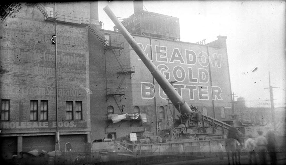 "View of a smokestack, hoists, and industrial buildings in Denver, Colorado; lettering reads: ""Meadow Gold Butter."" Between 1910 and 1925. (Charles Lillybridge/History Colorado/90.152.654 DPLY)