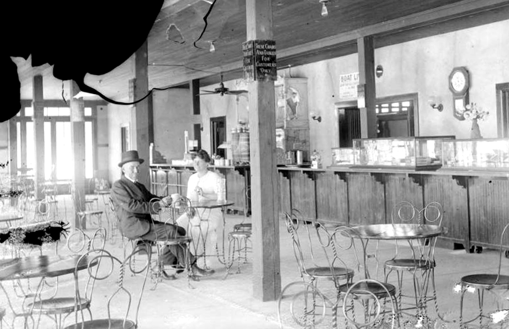 Interior view of City Park Pavilion, in Denver, Colorado; shows a man and woman, wire chairs, a soda fountain, ceiling fan, wall clock, and glass display cases. Between 1910 and 1925. (Charles Lillybridge/History Colorado/90.152.473 DPLY)