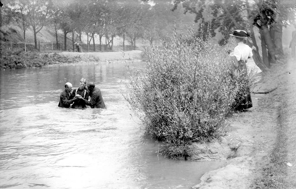 A man is baptized by two men in the South Platte River in Denver, Colorado. A woman stands nearby and watches. Between 1904 and 1915. (Charles Lillybridge/History Colorado/90.152.1297 DPLY)  history colorado; historic; denver public library; dpl; archive; archival; denverite