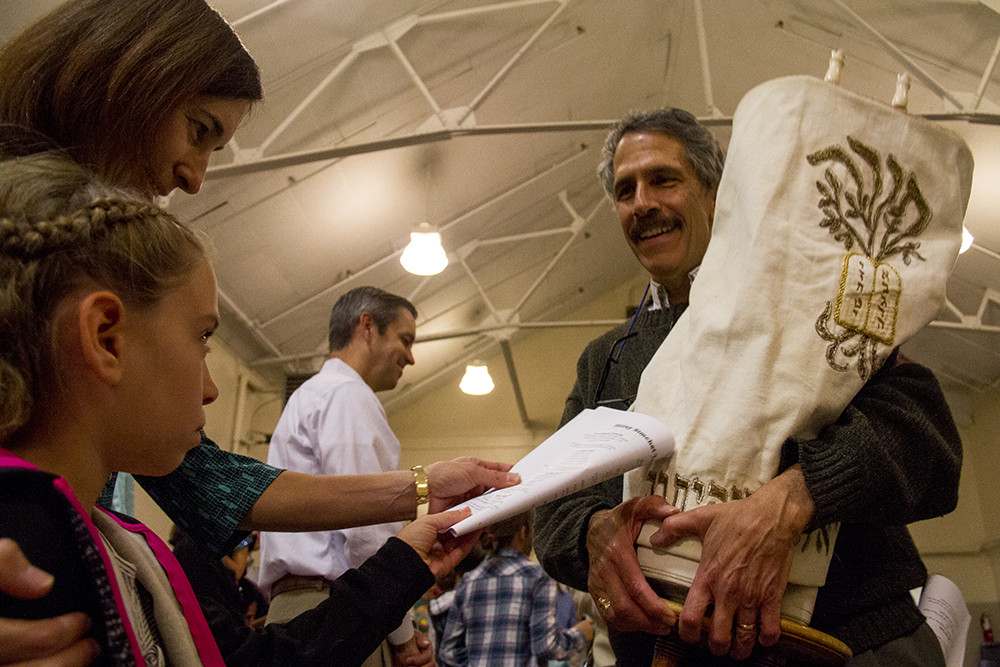 Temple Aaron parishoner Jack Rouff takes his congregation's Torah around the crowd at Temple Micah on the night when it is transferred into their care. (Kevin J. Beaty/Denverite)  religion; judaism; temple; torah; denver; colorado; kevinjbeaty; denverite
