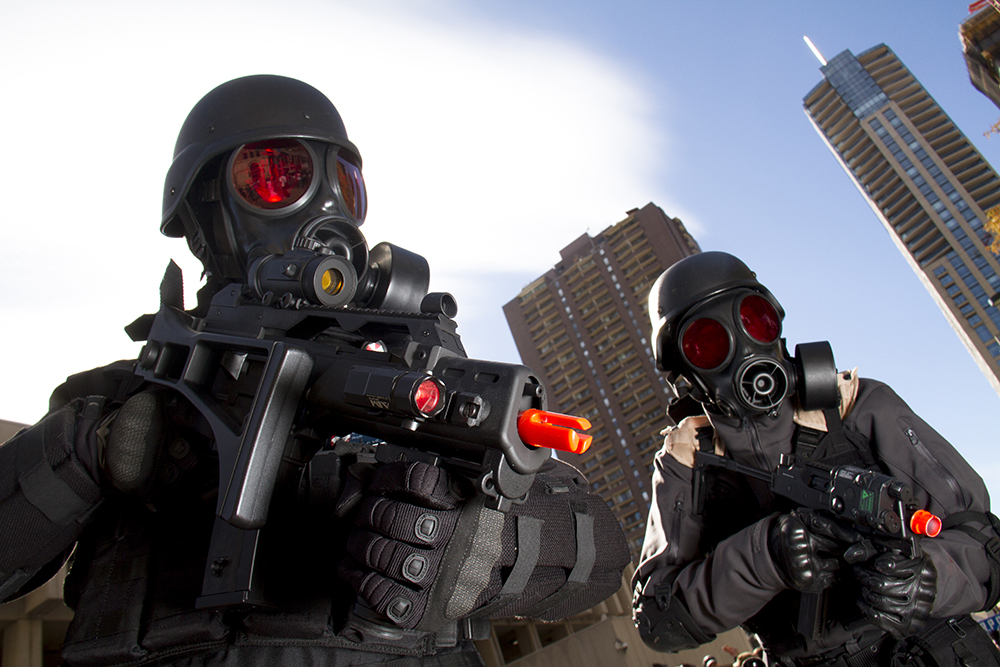 Umbrella Corp agents Eric Tocliff (right) and Robert Tolen brandishing rifles. Denver Zombie Crawl. Oct. 22, 2016. (Kevin J. Beaty/Denverite)  zombie crawl; halloween; cosplay; 16th street mall; sixteenth street; kevinjbeaty; denver; colorado; denverite; cbd;