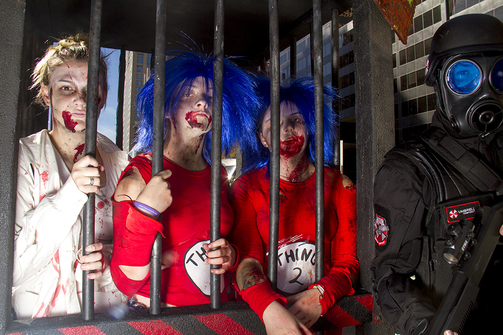 Hannah Jonsen, Hannah Troxler and Peyton Nagel pose locked up by Umbrella Corp agent Chris Weskamp. Denver Zombie Crawl. Oct. 22, 2016. (Kevin J. Beaty/Denverite)  zombie crawl; halloween; cosplay; 16th street mall; sixteenth street; kevinjbeaty; denver; colorado; denverite; cbd;