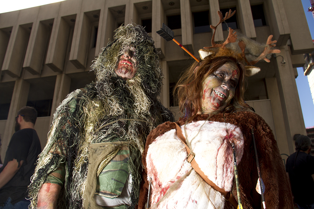 The undead hunter and his prey Darren Dunner (left) and Robbie Saunder. Denver Zombie Crawl. Oct. 22, 2016. (Kevin J. Beaty/Denverite)  zombie crawl; halloween; cosplay; 16th street mall; sixteenth street; kevinjbeaty; denver; colorado; denverite; cbd;