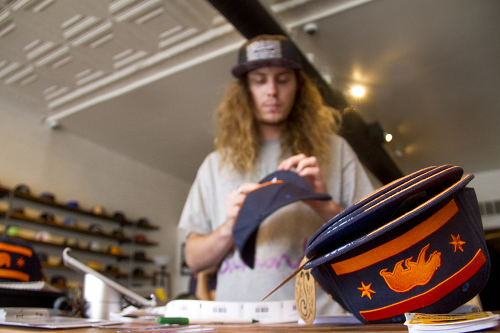 Grassroots California sales associate Connor Cook snaps hats. (Kevin J. Beaty/Denverite)  santa fe arts district; retail; commercial; denver; colorado; denverite; kevinjbeaty;