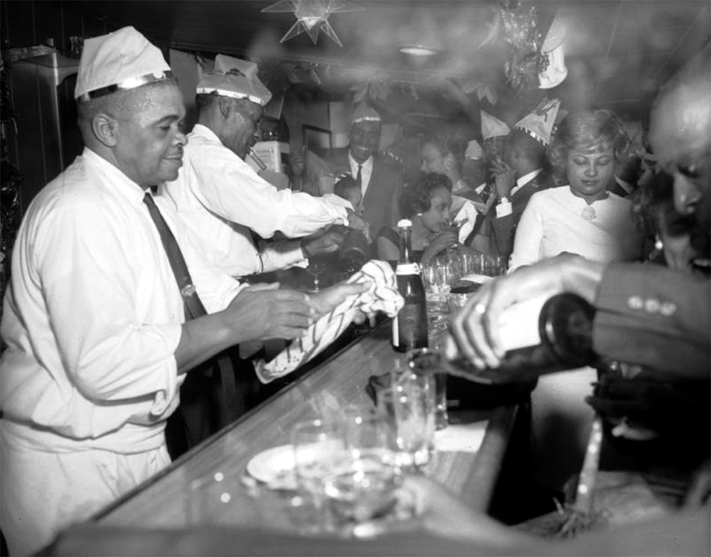 A group of African American (Black) men and women revelers gather at a bar on New Years Eve in Denver, Colorado. Many of the men wear party hats. One man has a cigar in his mouth and the room is filled with smoke. A bottle of champagne and empty glasses are on the bar. Decorations hang from the ceiling. Circa 1965. (Burnis McCloud/Denver Public Library/Western History Collection/MCD-199)  five points; historic; denver public library; dpl; archive; archival; denverite