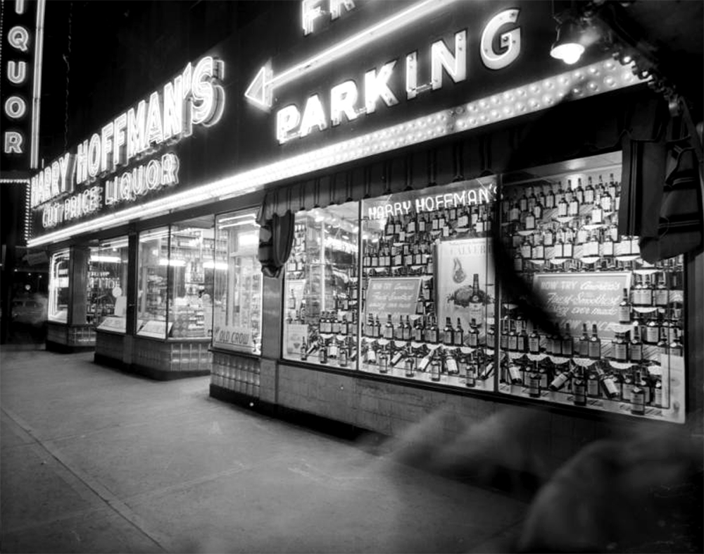 "Night view of Harry Hoffman's Cut Price Liquor store at Curtis and 18th (Eighteenth) Streets in Denver, Colorado. Windows display bottles of Calvert whiskey; neon signs read ""Harry Hoffman's"" ""Liquor"" and ""Free Parking."" Between 1950 and 1960. (Burnis McCloud/Denver Public Library/Western History Collection/MCD-3)  five points; historic; denver public library; dpl; archive; archival; denverite"