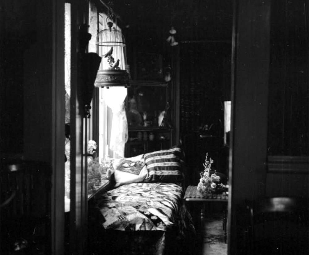 Image of a dark bedroom in the Prosser house in Central City that is illuminated only by the sunlight from the window. Between 1960 and 1980. (Sandra Dallas/Denver Public Library/Western History Collection/X-2898)  history colorado; historic; denver public library; dpl; archive; archival; denverite